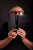 Man hides behind big sleek leather book. Old man with beard and big nerd glasses hides behind big sleek leather book royalty free stock images