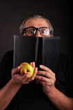 Man hides behind big sleek leather book. Old Man with beard and big nerd glasses showing apples in hand hides behind the black leather book Royalty Free Stock Images