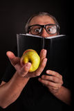 Man hides behind big sleek leather book. Old Man with beard and big nerd glasses showing apples in hand hides behind the black leather book Stock Photos