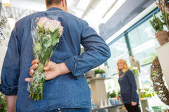 Man Hides Bouquet From Woman In Flower Shop. Rear view of men hides bouquet of roses from women in flower shop Stock Photo