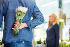 Man Hides Bouquet From Woman In Flower Shop Royalty Free Stock Images