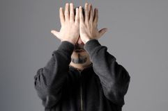 Man hides his face. Man dressed in black hides his face behind his hands royalty free stock photos