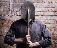 A man hides his face behind a shovel. Royalty Free Stock Images