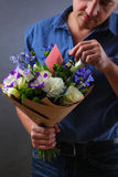 Man hides a note in the bouquet Royalty Free Stock Photo