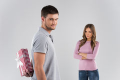 Man hides present behind back from his pretty girlfriend. Stock Photos