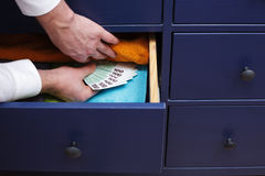 Man hides a salary in euros in a drawer Stock Images