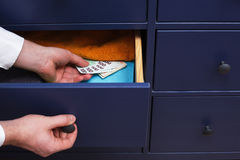 Man hides a salary in euros in a drawer Royalty Free Stock Photo