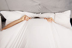 Man hiding in bed under sheets. Funny man hiding in bed under the sheets Royalty Free Stock Photography