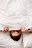 Man hiding in bed under sheets. Funny man hiding in bed under the sheets Royalty Free Stock Photo