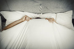 Man hiding in bed under sheets. Funny man hiding in bed under the sheets Royalty Free Stock Images