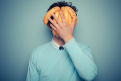 Man hiding behind bananas. A young man is hiding his face behind a bunch of bananas Stock Images