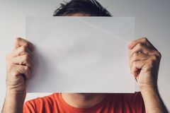 Man hiding behind blank white paper Stock Images