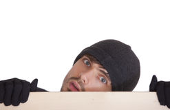 Man hiding behind board. Man in black hat hiding behind wooden board Stock Images