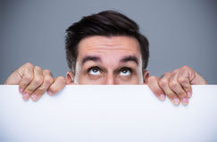 Man hiding behind a copy space Stock Images