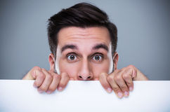 Man hiding behind a copy space Royalty Free Stock Images