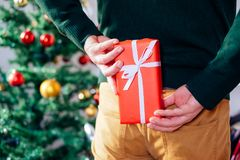 Man hiding behind his back a christmas gift box. Man ready to give a christmas present hidden by his back Royalty Free Stock Images