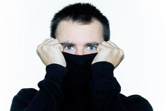 Man hiding behind his turtle polo neck afraid Stock Image