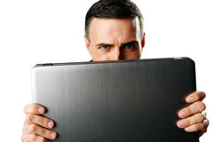 Man hiding behind laptop Royalty Free Stock Images
