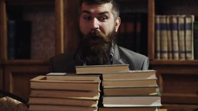 Man hiding behind a stack of books. Young surprised student hide behind stacked books. Close Up portrait of male student. Peeking over of pile of books in stock footage
