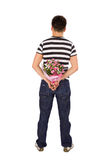 Man Hiding Bouquet of Flowers. Casual young man standing back to the camera hiding bouquet of flowers behind his back, isolated on white background Stock Image
