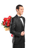 Man hiding a bouquet of flowers behind his back. Man wearing suit and bow tie hiding a bouquet of flowers behind his back isolated on white background Royalty Free Stock Images