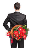 Man hiding a bouquet of flowers behind his back. Man wearing black suit hiding a bouquet of flowers behind his back isolated on white background Royalty Free Stock Images