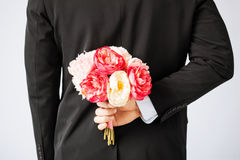 Man hiding bouquet of flowers. Behind his back Stock Photography