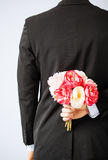 Man hiding bouquet of flowers Stock Images
