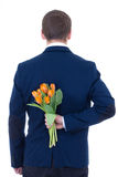Man hiding bouquet of flowers behind his back isolated on white. Background Royalty Free Stock Photos
