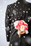 Man hiding bouquet of flowers Royalty Free Stock Image