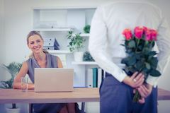 Man hiding bouquet in front of businesswoman at desk Stock Images
