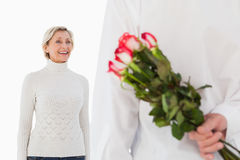 Man hiding bouquet of roses from older woman. On white background Royalty Free Stock Photos