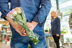 Man Hiding Bouquet Of Roses From Woman In Flower. Rear view of men hiding bouquet of roses from women in flower shop Royalty Free Stock Photo