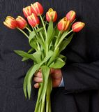 Man hiding bouquet of tulips behind back Royalty Free Stock Photo