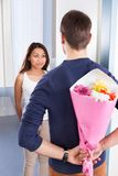 Man hiding bouquet from woman Royalty Free Stock Photos