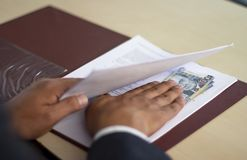 Man hiding bribe under some papers, Peruvian money stock image