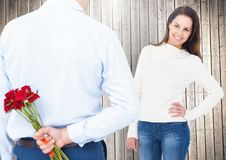 Man hiding bunch of roses from woman. Against digitally generated wooden plank background Royalty Free Stock Photos