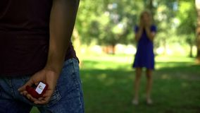 Man hiding engagement ring behind, ready to propose, worrying about answer. Stock photo stock photo