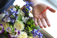 Man hiding the engagement ring in a bouquet Stock Photography