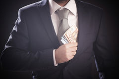 Man hiding euro banknotes in his  jacket Stock Images