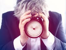 Man hiding face behind alarm clock on white background. stock images