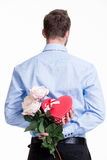 Man hiding a flower behind his back. Man hiding a flower behind his back isolated on white background Royalty Free Stock Images