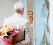 Man hiding a  flower bouquet for a surprised woman Royalty Free Stock Photos