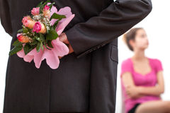 Man hiding flowers. A man hiding a bunch of flowers for his girlfriend behind his back Stock Image