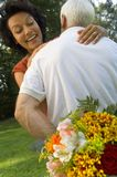 A man hiding flowers from his wife. Stock Photography