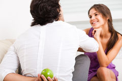 Man hiding fruit from his girlfriend. Young couple sitting on the sofa,man hiding fruit from his girlfriend royalty free stock photos
