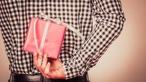 Man hiding gift box behind back. Holiday surprise. Royalty Free Stock Photos