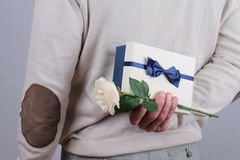 Man hiding a gift box and flower behind his back close up. Stock Images