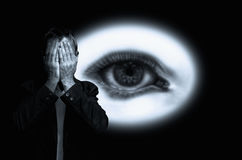 Man hiding his face on background with eye in white circle. Royalty Free Stock Image