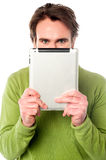 Man hiding his face with tablet device Stock Images